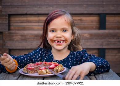 Young happy caucasian girl in dress holds on plate strawberry chocolate oatmeal pie, tasty cake ready to eat. Vegan sweet dessert, vegetarian healthy food. Chocolate smeared on face and dirty mouth.