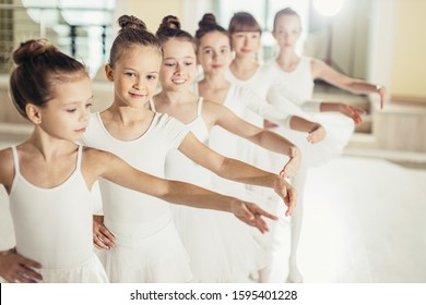 Young happy caucasian little ballerinas, awesome ballet dancers practicing some dance element in a dance class. Professional school of ballet dance for kids, chiildren