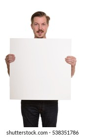 Young happy Caucasian man holding empty white board with copy space
