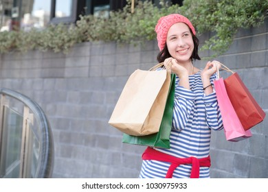 Young happy caucasian teenager holding colorful shopping bag in outdoor building city, smile woman enjoying shopping, lifestyle recreation time in weekend concept