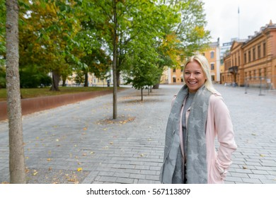 Young happy Caucasian woman smiling along peaceful city plaza