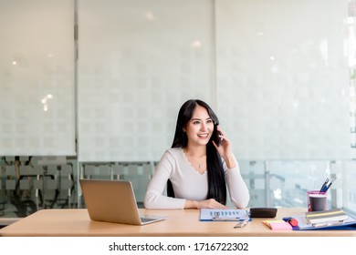 Young, happy, cheerful, bright, cute, beautiful business women with a smile on the phone, sitting in the house, in the office, using a laptop computer, work at home concept.