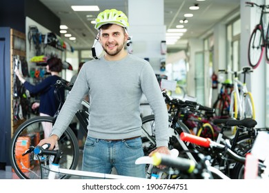 Young happy cheerful positive man in helmet standing with sport bicycle in bicycle store