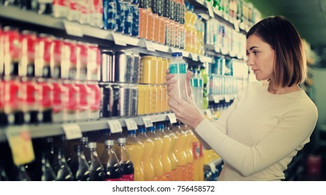 Young happy cheerful positive woman choosing refreshing beverages in supermarket