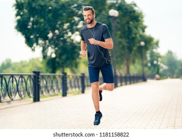 Young happy cheerful smiling man, during morning jogging outdoors. Fitness, sport, exercising and workout in city concept.