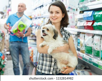 Young happy cheerful  smiling woman with dog in pet shop, during shopping with husband