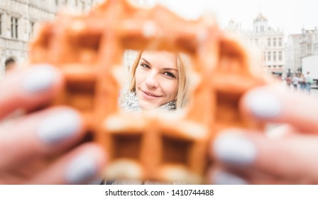 Young happy cheerful woman looking at the camera through a hole in the Belgian waffle against the backdrop of the Grand Place in Brussels, Belgium.