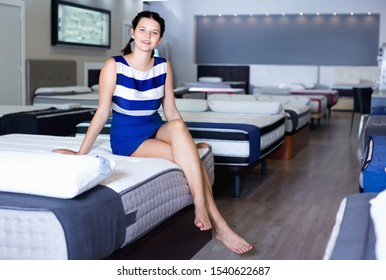 Young happy cheerful woman is sitting on bed and testing mattress in the store.