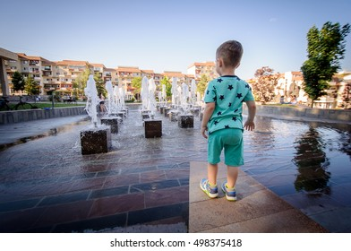 Young happy child boy looking at the water fountain