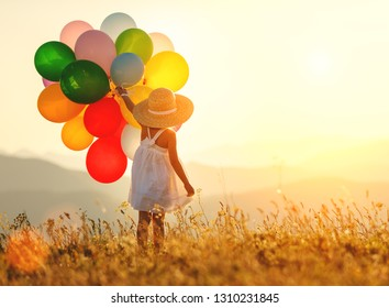 young happy child girl with balloons at sunset in summer