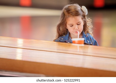 young happy child girl drinking juice in a cafe