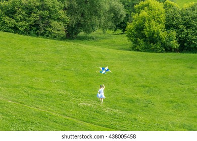 young happy child girl playing with bright kite in park. summer holiday vacation
