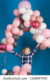 Young happy child lets pink, grey and white ballons to fly in a high on blue background. Child jumps to catch his ballons. Ballons for holiday, celebration, anniversary as decorations and games