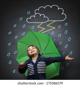 Young happy child singing and dancing holding an umbrella standing in front of a chalk drawing of a rain and lightning storm on a school blackboard