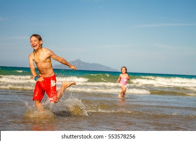 young happy children - boy and girl - having fun on sand beach, sea background