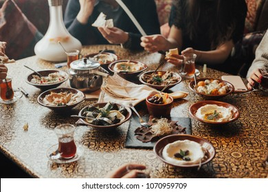 Young happy company of people is eating lebanon food and smokinh shisha. Lebanon cuisine. Traditional meze lunch