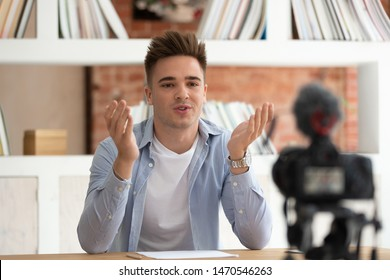 Young happy confident cool male student sitting at table in front of camera, recording self-introduction video for scholarship or educational grant achievement. Millennial guy sharing studying tips.
