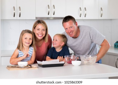 young happy couple baking together with little son and young beautiful daughter at home kitchen having fun playing with cream in family lifestyle and nutrition education concept