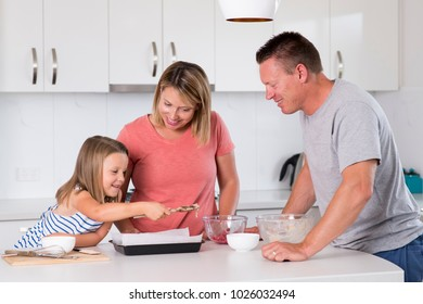 young happy couple baking together with little young beautiful daughter at home kitchen having fun playing with cream in family lifestyle and nutrition education concept