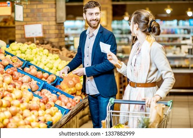 Young and happy couple buying fresh fruits standing together with shopping list and cart in the supermarket