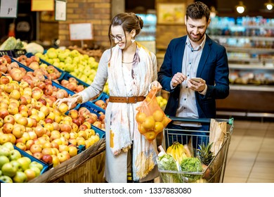 Young and happy couple buying fresh fruits and vegetables standing together with shopping cart in the supermarket