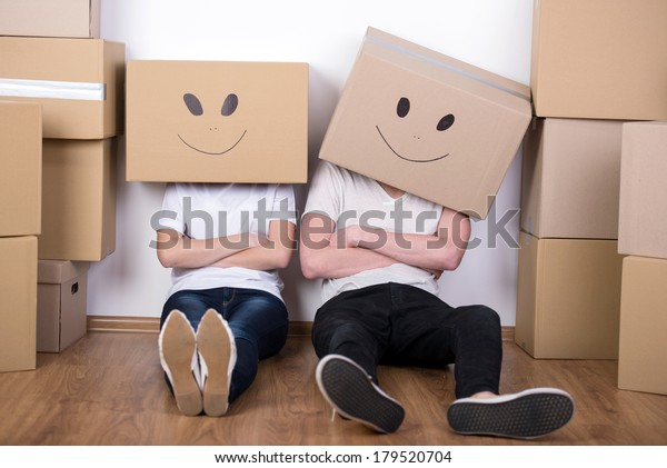 Young happy couple with cardboard boxes on their heads happy his new home