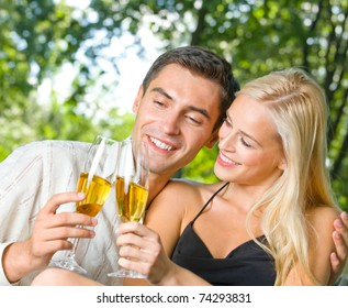 Young happy couple celebrating with champagne, outdoors