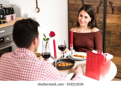 Young happy couple celebrating Valentine's day with a dinner at