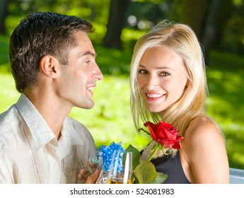 Young happy couple with champagne, gift and rose, outdoors. Love, flirt, romantic, relations, celebration theme concept.