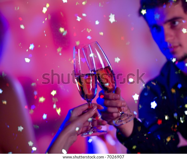 Young happy couple with champagne glasses at celebration. Focus on glasses.