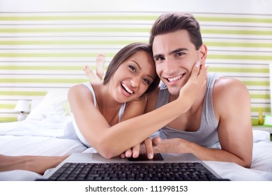 Young happy couple chatting over laptop, close-up