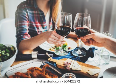 Young happy couple cheering with glasses of red wine, family dinning at home, traditional and toasting concept, filtered image