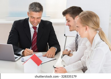 Young Happy Couple Consulting Estate Agent For House