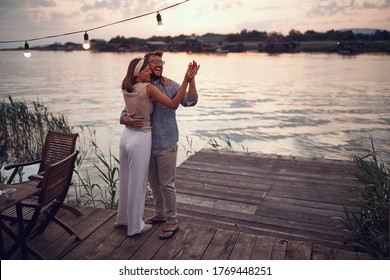 young happy couple dancing by the river at sunset