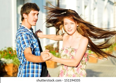 Young happy couple dancing on street outdoors