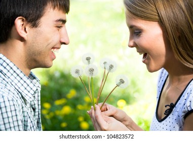 Young happy couple with dandelions