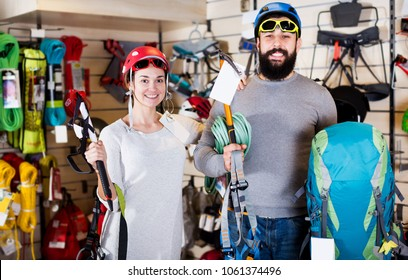 Young happy couple deciding on climbing equipment in sports equipment store