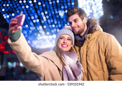 Young and happy couple doing winter selfie outdoor. Soft focus. Christmas and New Year concept