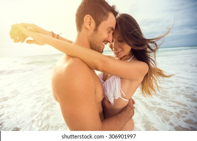 young happy couple with draw heart on tropical beach. Honeymoon