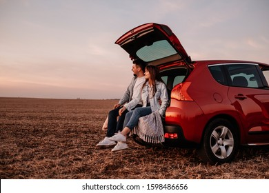 Young Happy Couple Dressed Alike in White Shirt and Jeans Sitting at Their New Car Trunk, Beautiful Sunset on the Field, Vacation and Travel Concept