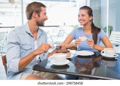 Young happy couple eating cake together in the cafe