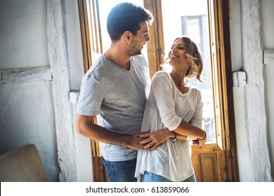 Young happy couple embracing while dancing and looking at each other against window.