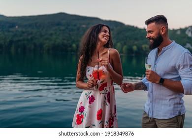 Junge glückliche Paare, die bei Sonnenuntergang am Fluss genießen