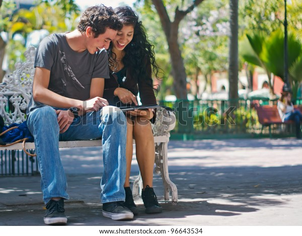 Young happy couple enjoying looking at an electronic pad