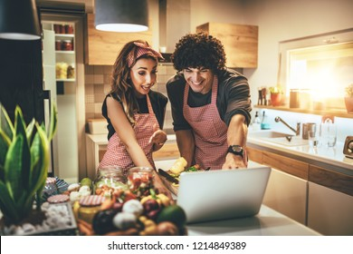 Young happy couple is enjoying and preparing healthy meal in their kitchen and reading recipes on the laptop.