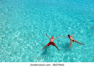 Young happy couple floating in the turquoise ocean