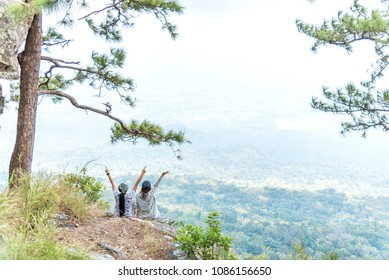 Young happy couple girl spreading hand on top mountain and enjoying forest valley view.