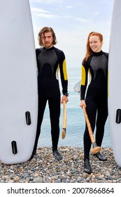 Young happy couple have fun standing on beach, preparing for stand up paddleboard. Acitve man and woman in wetsuit lead Healthy lifestyle. Water sport, SUP surfing tour in beach vacation