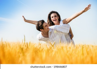 Young, happy couple have a piggy back in the wheat field.Summer season