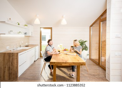 Young and happy couple having a breakfast sitting at the wooden table of the dining room of the modern country house. Wide angle view